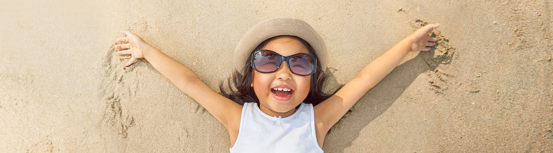 Small girl with sunglasses and hat laying on sandy beach