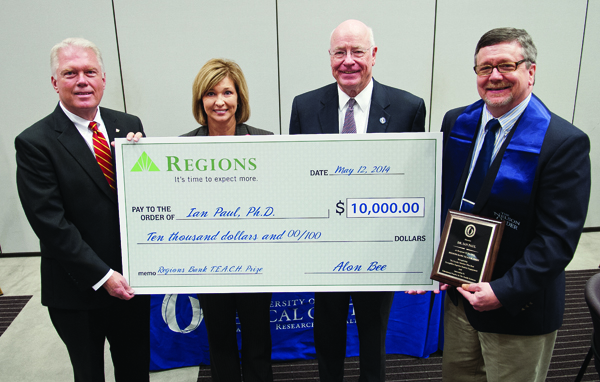 As the winner of the second annual TEACH Prize, Dr. Ian Paul, far right, professor of psychiatry and human behavior, receives a ceremonial check from Alon Bee, far left, Regions Bank Metro Jackson president. With them are Dr. LouAnn Woodward, associate vice chancellor for health affairs, and Dr. James Keeton, vice chancellor for health affairs.