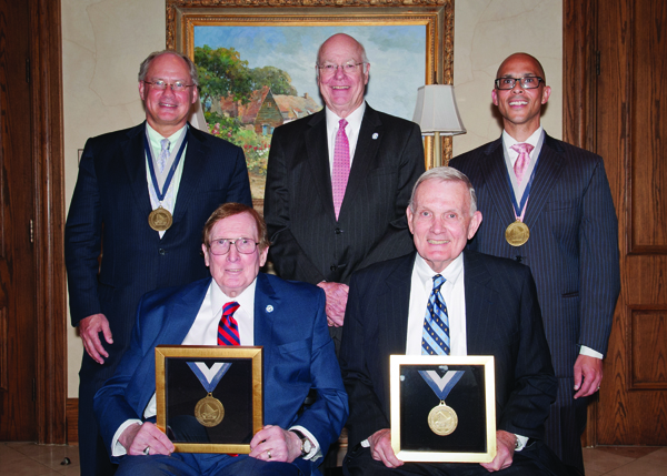Dr. William Geissler, standing, left, and Dr. George Russell, standing, right, were named recipients of, respectively, the Alan E. Freeland Chair of Orthopedic Hand Surgery and the James L. Hughes Chair of Orthopedic Surgery. The chairs are named in honor of Dr. Alan Freeland, seated, left, and Dr. James Hughes, seated right; each is a professor emeritus at UMMC. Dr. James Keeton, standing, center, vice chancellor for health affairs and dean of the School of Medicine, gave the welcoming remarks at a reception held June 11 at the Country Club of Jackson. Geissler is a professor in the Department of Orthopedic Surgery and Rehabilitation. Russell is professor and chair of the Department of Orthopedic Surgery and Rehabilitation.