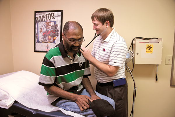 In one of his father's old examining rooms, Dr. Sam Holdiness takes his time with patient Rickie Parks.