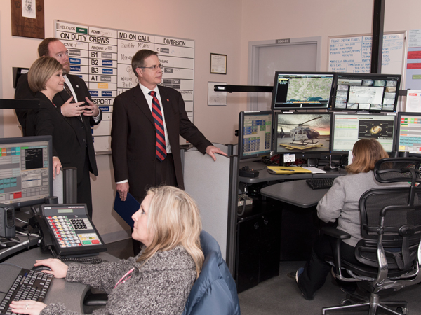 Woodward (upper left) and Wilson chat with Vitter (center), during a visit to Mississippi MED-COM. The communications hub's staff includes EMT basic Tammy Holliman (seated left) and communications specialist Samantha Tucker.