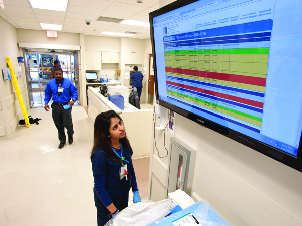 Deepali Bhatt, an emergency room technician, stops to scan an electronic board that details patients en route via ambulance to the Emergency Department.