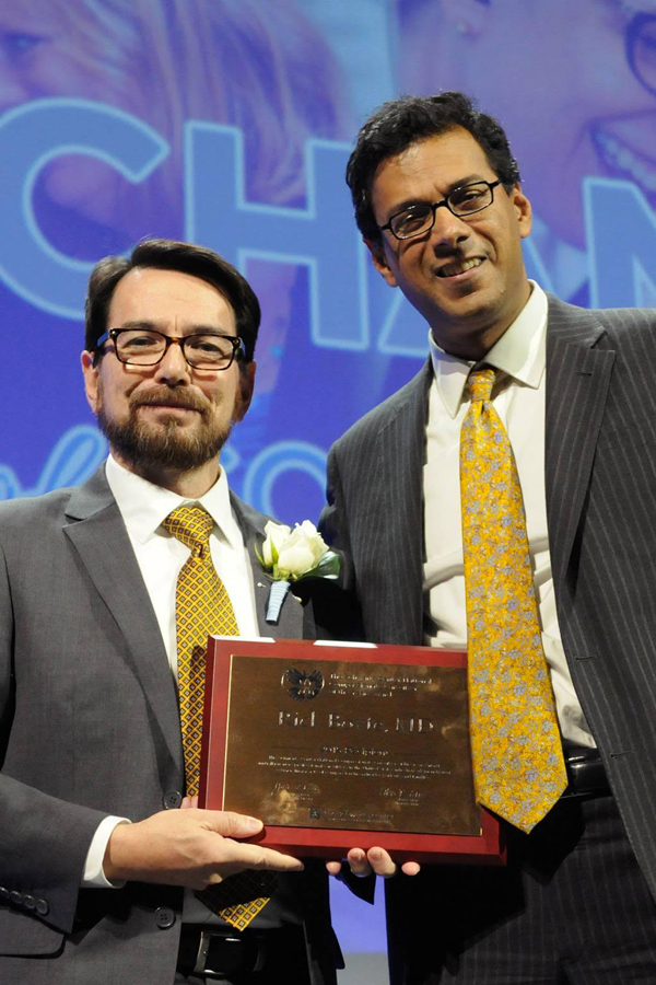 Boyte, left, is congratulated by surgeon and author Dr. Atul Gawande. Photo courtesy of Randy Goodman.