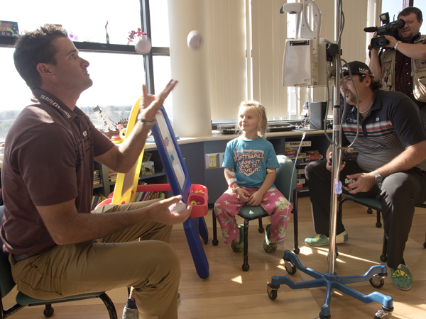 PGA golfer Sam Saunders took up juggling during a visit to Batson Children's Hospital. Looking on are, from left, patient Kimber Norris of Moselle, PGA golfer Andres Gonzales and Drew Hall of WJTV.