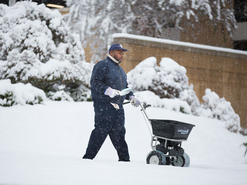 Kinard Anthony, groundskeeper, spreads deicer on the sidewalks in front of the hospital.