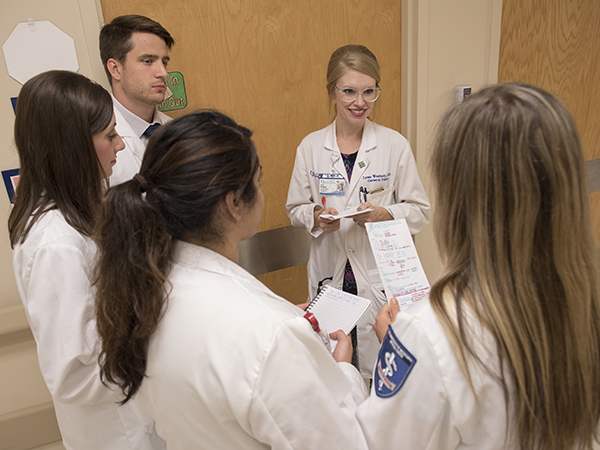 Lyssa Weatherly, center, assistant professor of medicine, with third year medical medical students.