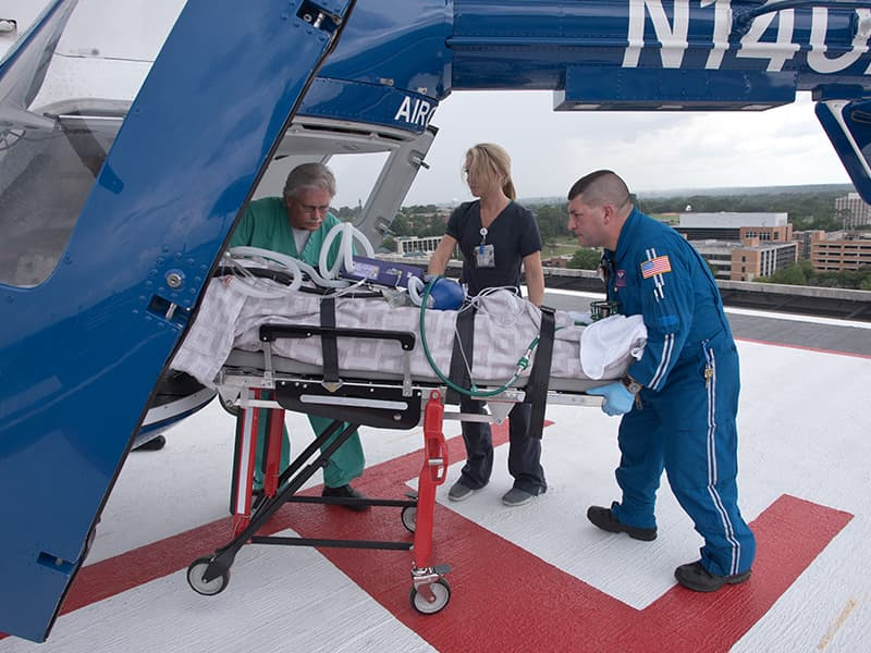Summers, left, oversees the unloading a patient from the AirCare helicopter, with Jazz Kolb, an R.N. in the Emergency Department, and Paul Boackle, flight/transport R.N.