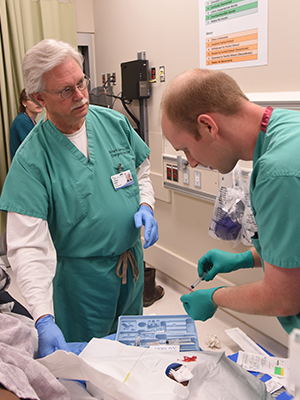 Summers and Dr. Ryan Green, an Emergency Medicine resident, tend to a patient in the ER.