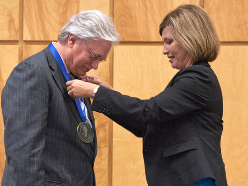 Dr. LouAnn Woodward, right, vice chancellor for health affairs and dean of the school of medicine, awards the Billy S. Guyton Distinguished Professor medallion to Dr. Richard Summers in June 2015.