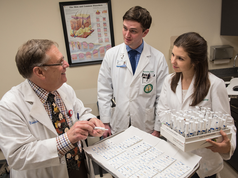 Dr. Stephen Helms, professor of dermatology, teaches a patch-testing technique to detect substances that cause allergic contact dermatitis to medical students Brandon Bodie and Jordan Keely, both in their fourth year at the University of Alabama-Birmingham.