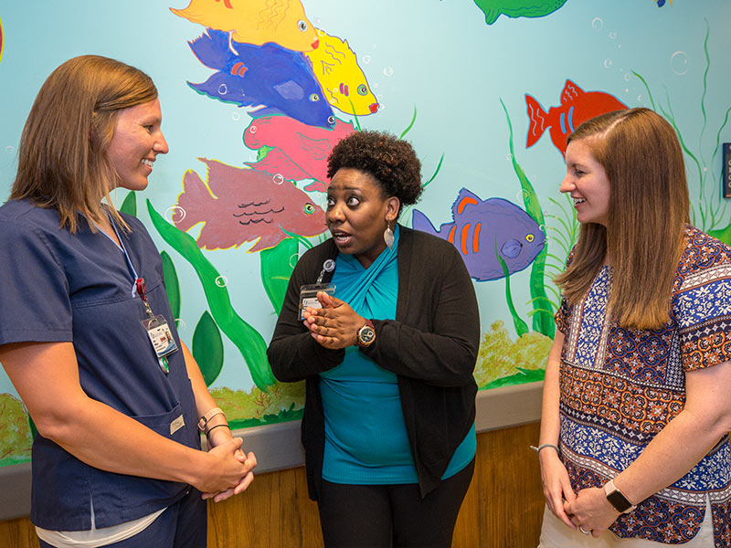 Dobbins talks to friends, Katie Williams, left, a nurse and pediatric care coordinator, and Sarah Elkin, a nurse practitioner in the pediatric hematology and oncology division.