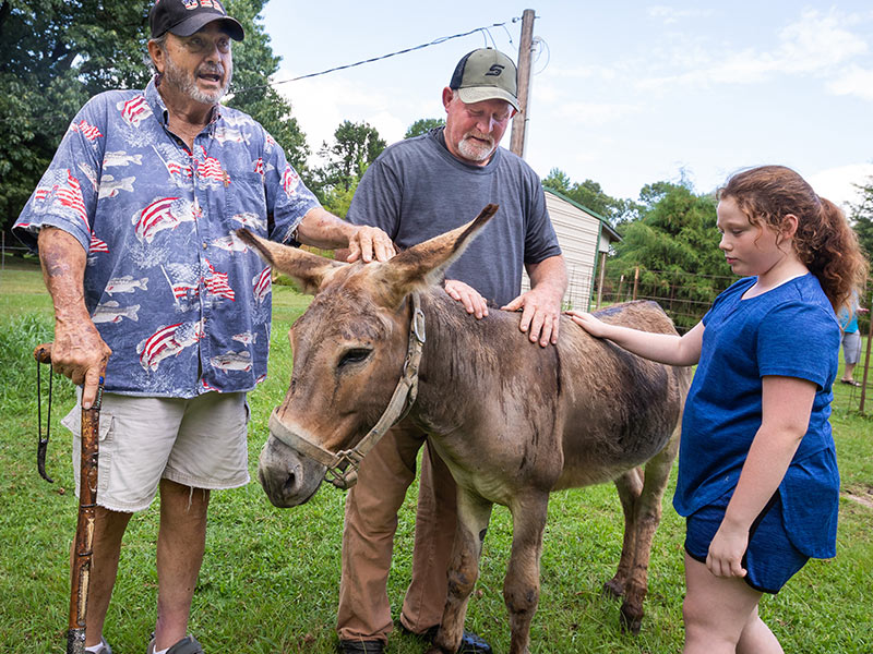 From left, Eupora residents Ray Gustafson, his neighbor Dale Wilson, Ray's granddaughter Haley Blount, and Bobo the donkey.