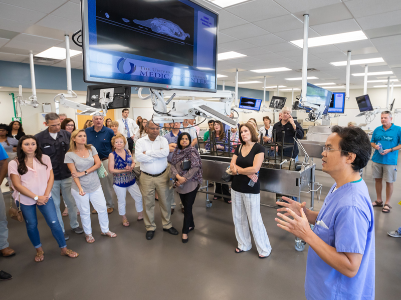 Dr. Yue Lu, right, assistant professor of neurobiology and anatomical sciences, gives a Family Day tour group a quick lesson on the features of the Gross Anatomy Lab.