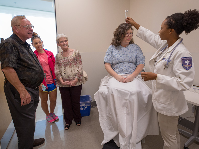 Family members of incoming students were taken to different locations throughout the school giving them a preview of what is to come for their first few years before seeing patients bedside. Here, family members, from left, Johnnie Whitaker, Shayna Smith and Jimmie Whitaker watch a demonstration by fourth-year medical student Jasmine Padgett, right, with mock patient Karen Walling at the Judith Gore Gearhart Clinical Skills Center.