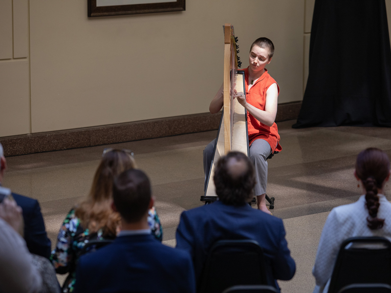 Harpist/vocalist Laura Pitts performs one of three musical selections.
