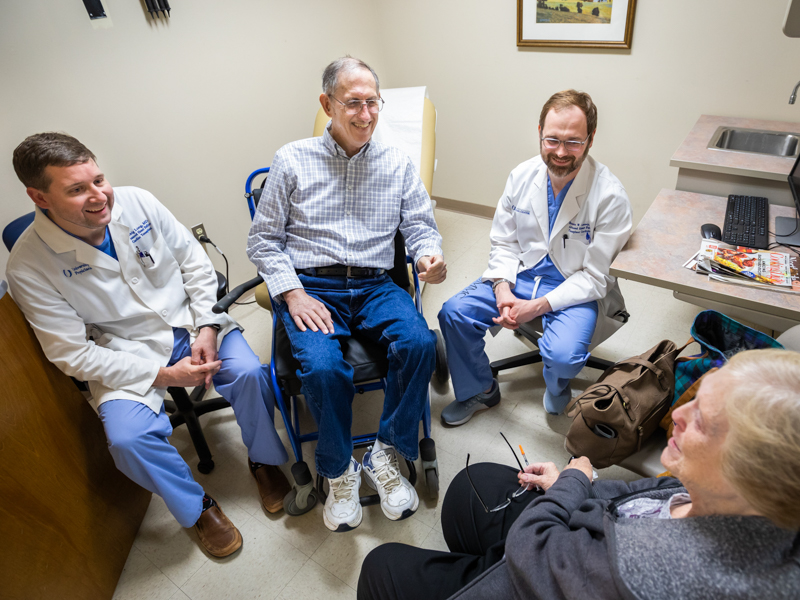 Fred Robertson, second from left, is among the cancer patients Dr. Craig Long, left, and Dr. Brandon Lennep, right, monitor for heart problems. Long and Lennep recentl discussed the results of his most recent screening with Robertson and his wife, Sue.