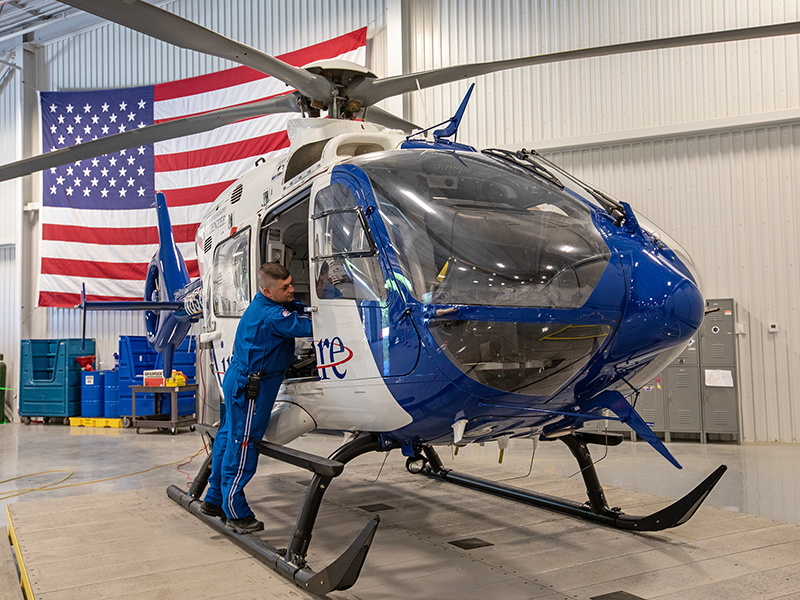 Paul Boackle, a flight nurse with AirCare, readies the helicopter for its next trip while it's temporarily parked at the new MCES building.