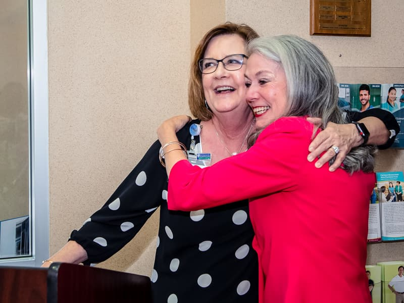 Harris shares a hug with Terri Gillespie, chief nursing executive and clinical services officer, at the School of Nursing retirement reception.
