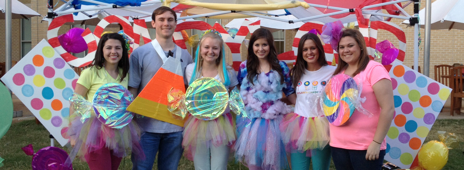 Group of male and female students pose for candy land event in colorful costumes.