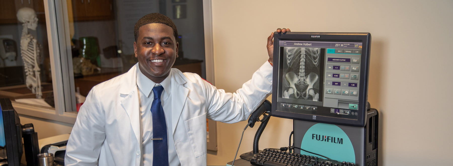 Male radiologic sciences student poses in front of equipment.