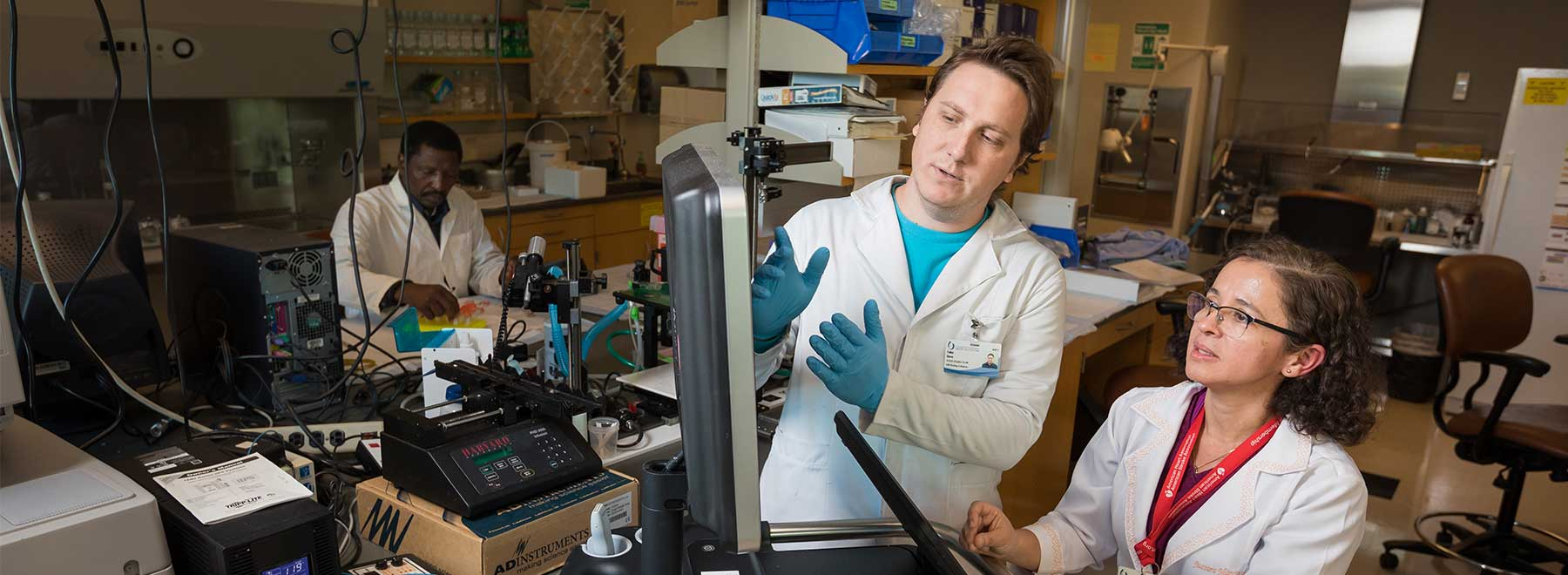 Two researchers work with scientific equipment