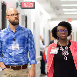 Male and female talk while touring clinical trials research unit