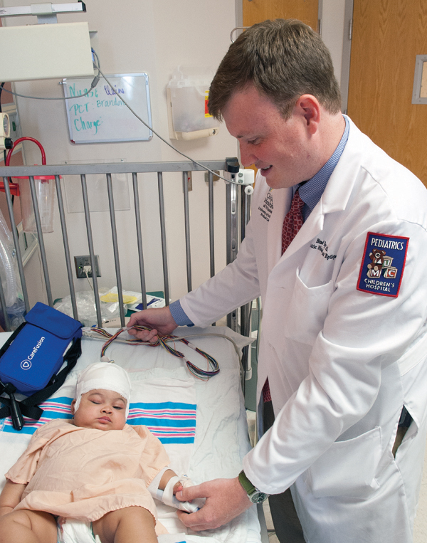 Dr. Brad Ingram, assistant professor of pediatric neurology, examines epilepsy patient Olivia Edwards.