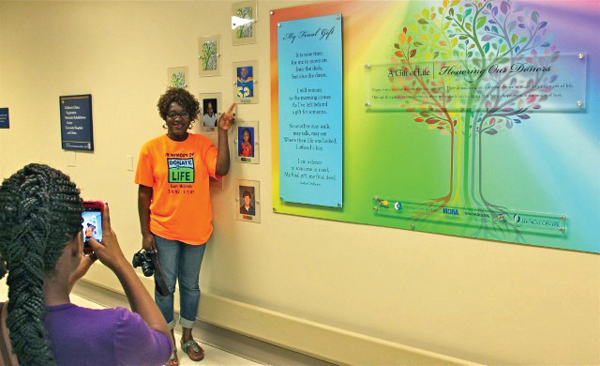 Jackie McInnis of Mount Olive has her photo taken next to the newly dedicated Wall of Heroes at Batson Children's Hospital, which honors pediatric organ donors including her son, Gary Lenzie McInnis.