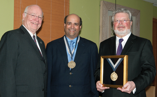 At an event to announce completed funding of the Paul H. Parker Chair of Pediatric Gastroenterology, Dr. Jimmy Keeton, left, vice chancellor for health affairs, presents medals to Dr. Paul Parker, right, and Dr. Neelesh Tipnis.