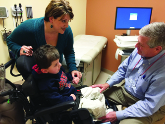Accompanied by his mom, Modesta Carroll, Levi Washington of Vancleave visits with Dr. John Purvis at UMMC's children's specialty clinic in Biloxi. Levi copes with physical and mental impairments stemming from an extremely rare chromosome abnormality.