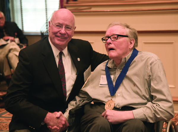 Dr. James Keeton, left, vice chancellor for health affairs and dean of the School of Medicine, congratulates Dr. Jack Aldridge Jr. of Brandon, a recipient of the Class of 1964 commemorative medal. Aldridge passed away in October.