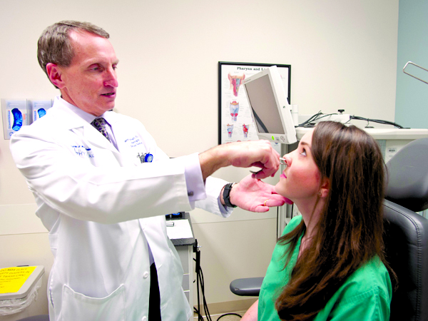 University Physicians (UP):  Dr. Scott Stringer, professor and chair of the Department of Otolaryngology and Communicative Sciences, examines Allison Pitts, a physician's assistant who is one of his patients.