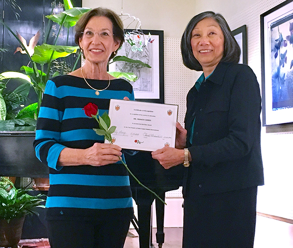 Gordy, left, receives the Red Rose Award from Betty Wong, Red Rose Award Committee chairperson, Tau Chapter Delta Kappa Gamma.