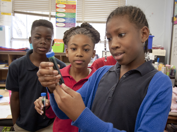 (From left) Kristopher Robinson, Kennedy Robinson and Akierah Walker watch as a bleach solution begins to change to clear the green color in a tube of water.