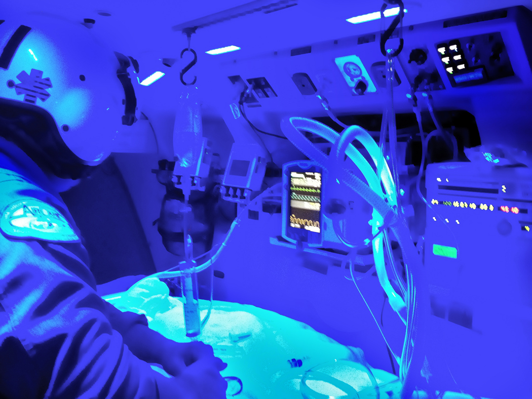 AirCare flight critical care paramedic Jeremy Benson monitors a critically ill patient who is on a ventilator during a recent flight to the University of Mississippi Medical Center. Paramedics onboard the medical flight helicopter often wear night-vision goggles and use a blue-tinted interior light, which allows them to navigate safely to inter-facility transports or emergency scenes.