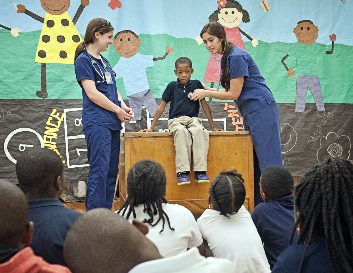 Senior nursing students Kelly Wilson, left, and Julia Lake Landrum, right, demonstrate how to check third-grader Adyn Bolds' vital signs for his classmates at Brown Elementary School.
