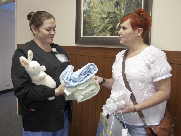 Battle, right, a year and eight months after receiving a new liver, gives her transplant coordinator Katherine Savoy a gift in preparation for the birth of Savoy's baby.