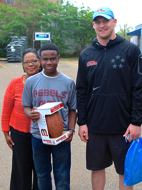 Jacob Partlow of Jackson holds on to his new autographed football from former Ole Miss quarterback Bo Wallace. With help from Jacob's mom, Olevia Williams, left, Wallace surprised Jacob with the football Friday afternoon.
