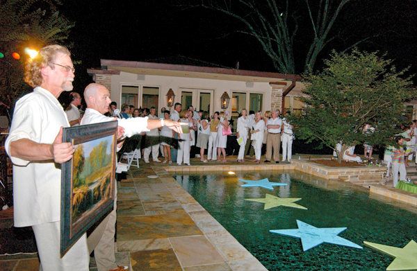 Volunteers encourage bidding on a piece of original artwork during a live auction at the 2005 Enchanted Evening.