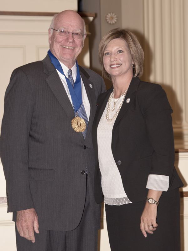 Dr. James Keeton, left, wears the medallion he has just received from his successor, Dr. LouAnn Woodward, vice chancellor for health affairs and dean of the School of Medicine.