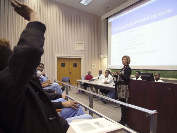 A student, far left, prepares to pose a question for Dr. LouAnn Woodward