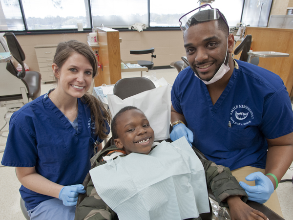 Second-year dental student Brittany Varney, left, and third-year dental student Christopher Cathey, right, put a grin on Galloway Elementary student Antwuan Williams' face .