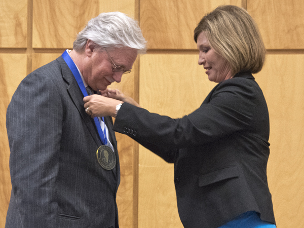 Dr. LouAnn Woodward, right, vice chancellor for health affairs and dean of the school of medicine, hangs the Billy S. Guyton Distinguished Professor medallion on Dr. Richard Summers, associate vice chancellor for research.