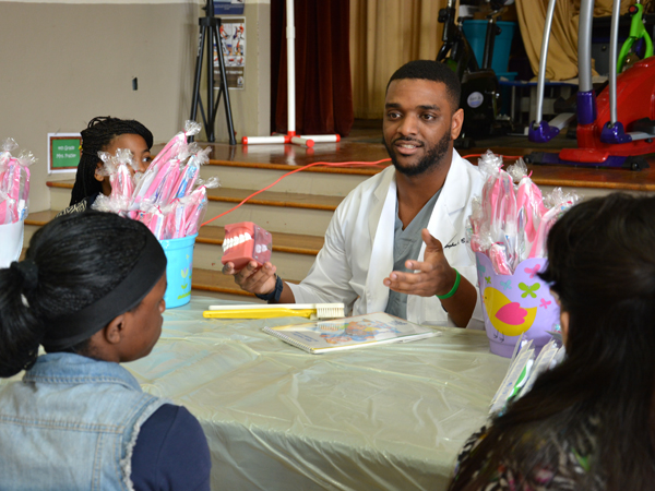 Chris Cathey, third-year dental student, instructs young students on how to properly brush their teeth.
