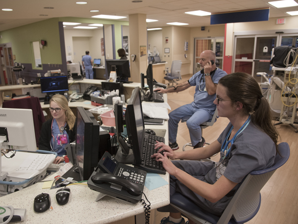 (From left) Registered nurses Carsyn Byars, Danny Smith and Kelly Green input information about patients being seen in the Pediatric Emergency Department.