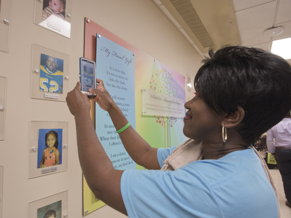Jackie McInnis of Mount Olive takes a photo of her son Gary's display on the pediatric Wall of Heroes.