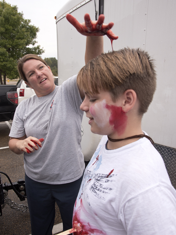 Paula Vital, a nurse educator in UMMC's Center for Emergency Services, drips fake blood on the head of Northwest Rankin Middle School student Chris Russell