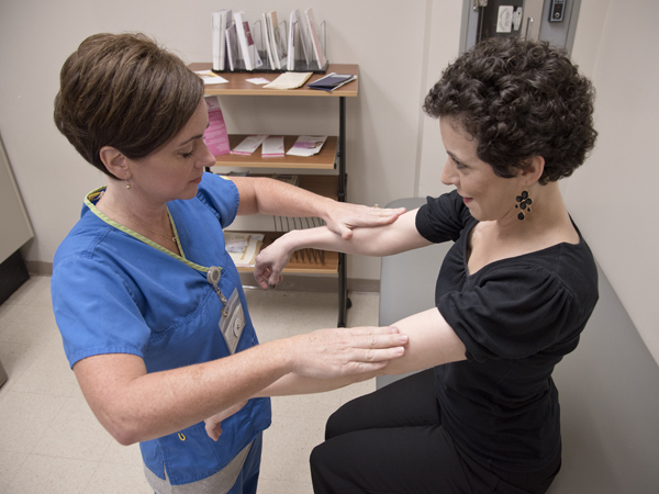 Patients who undergo treatment for breast cancer can suffer from loss of strength and range of motion. Vining, left, performs manual muscle testing reassessment of shoulder flexion for patient Sara Harvey Roberts.