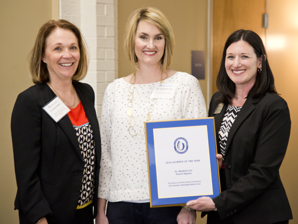 Carr, center, is recognized as Alumnus of the Year at the 2016 SHRP Alumni Day and Continuing Education event April 1 by dean of the school Dr. Jessica Bailey, left, and Megan James, Alumni Engagement Associate.