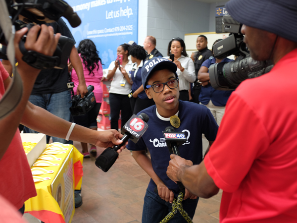 Morgan receives the celebrity treatment by Walmart employees and Jackson-area media after his arrival at the Clinton Walmart.